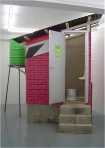 Versión 3 de Caracas: Dry Toilet. 2003.Materiales de construcción. 2.0 x 2.7 x 3.2 mt. Galerie Nordenhake, Berlín, Stockholm. 03 marzo – 17 abril, 2004. Cortesía de la artista y Galerie Nordenhake.